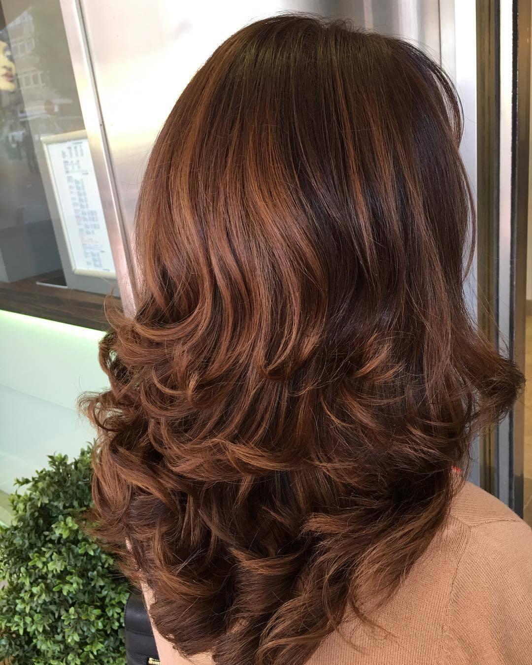 Femme aux cheveux châtains, coiffée dans un brushing
