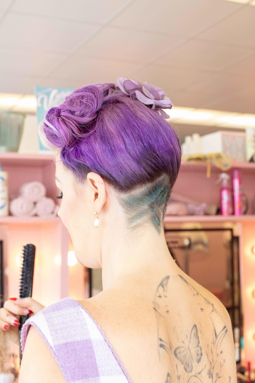 Coiffures vintage pour cheveux courts : Gros plan d'une femme aux cheveux violets courts, coiffée pour une victoire, enroulée avec une sous-coupe
