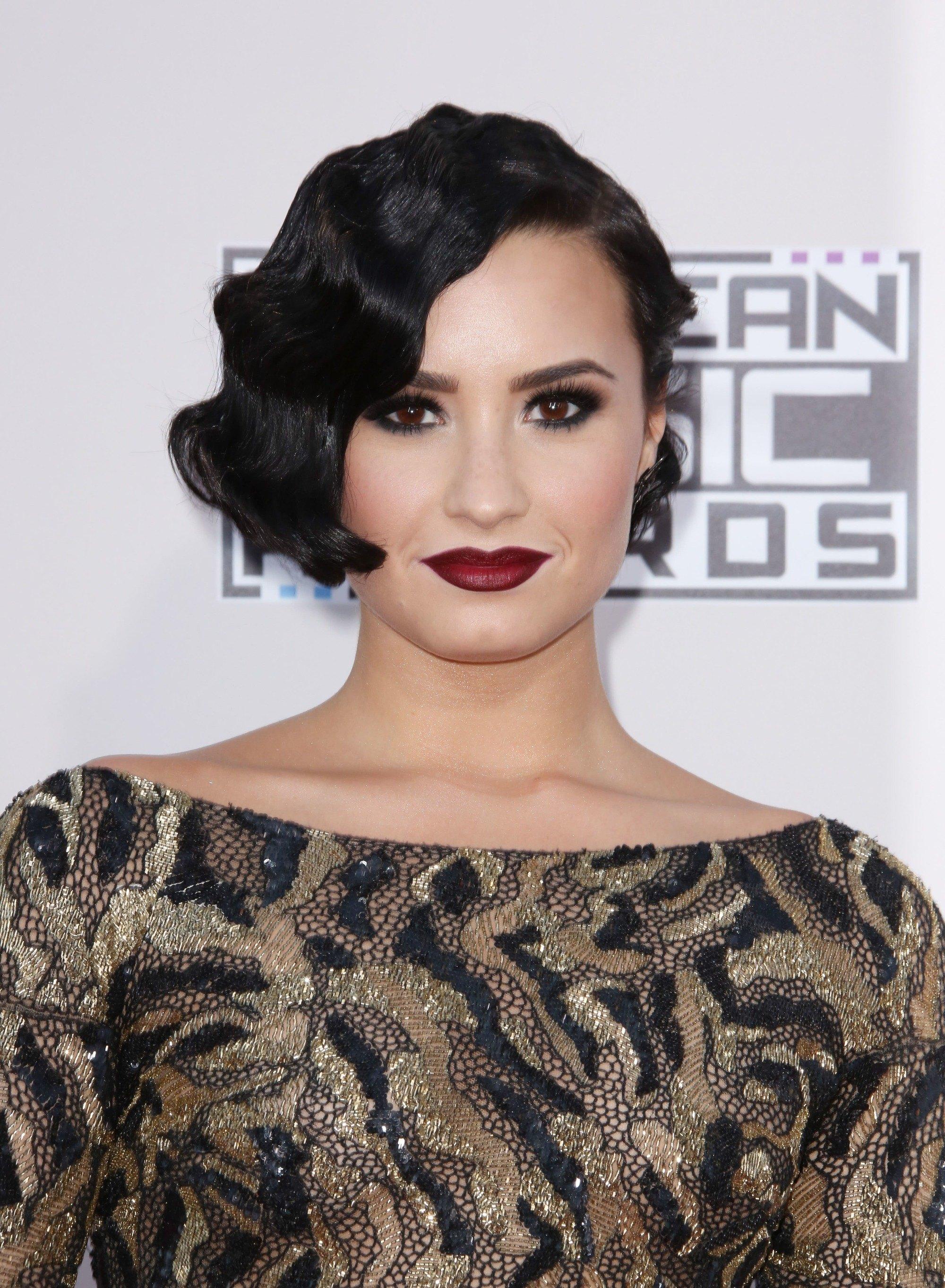 Cheveux courts vintage : Gros plan de Demi Lovato avec des cheveux courts brun foncé coiffés en un doigt ondulé sur le tapis rouge