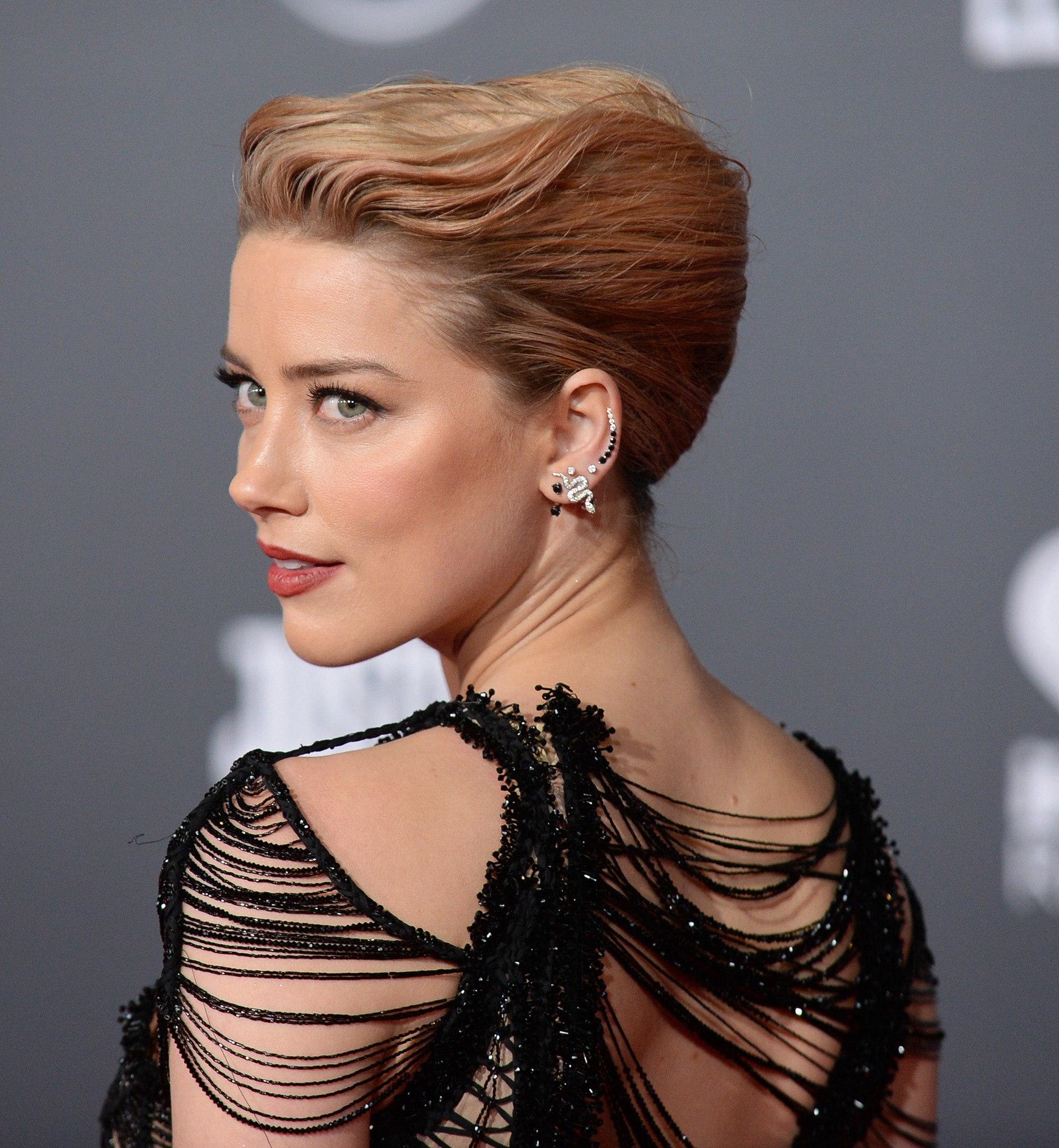 Cheveux courts vintage : Gros plan d'Amber avec une blonde fraise, coiffure à la française sur le tapis rouge