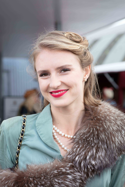Cheveux courts vintage : Gros plan d'une femme aux cheveux courts, coiffée à moitié, à moitié duvet, avec une veste bleu canard, des perles et un jet au festival de Goodwood