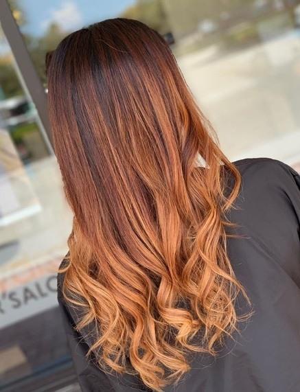 Femme avec de longs cheveux bouclés en cuivre de balayage