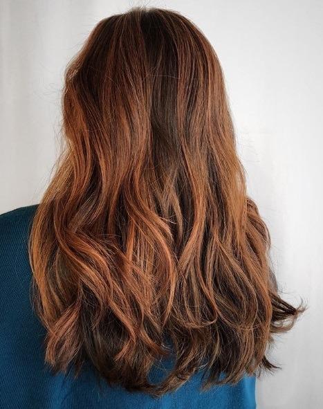 Femme aux cheveux mi-longueur auburn balayage