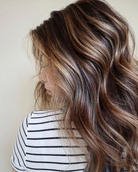 Femme aux cheveux bruns ondulés en balayage