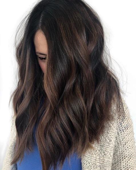 Femme aux cheveux mi-longs, ondulés, brun foncé, en balayage