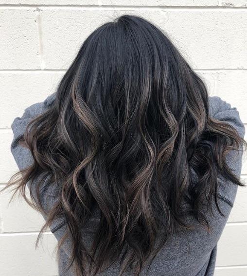 Femme aux cheveux noirs mi-longs et ondulés en balayage