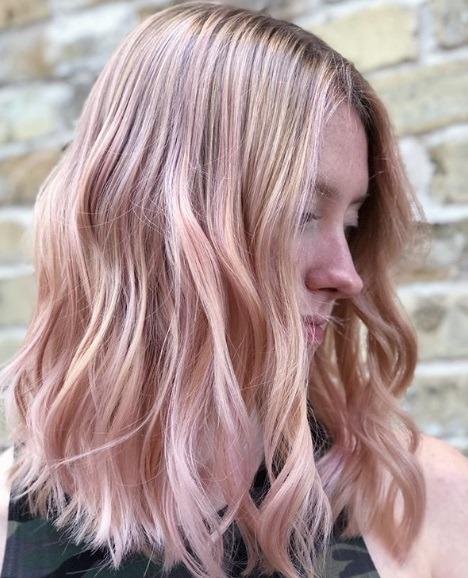 Femme aux épaules ondulées, cheveux rose clair en balayage