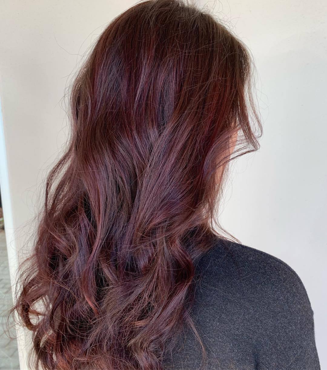Femme avec de longs cheveux bouclés acajou rouge balayage