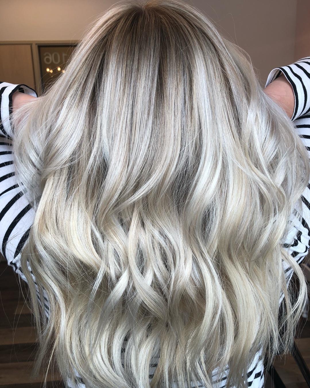 Femme aux longs cheveux ondulés et blonds perlés en balayage
