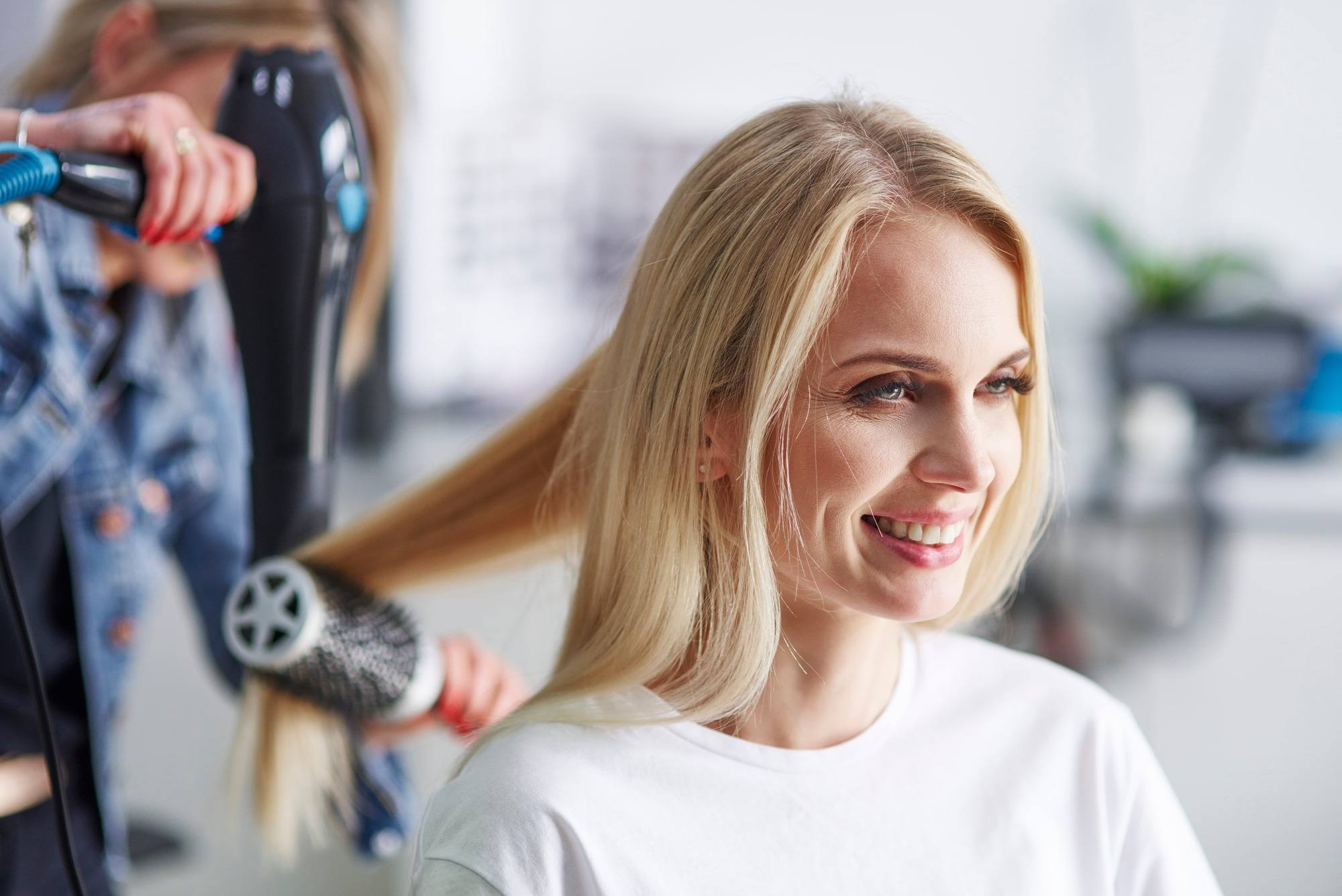 Une femme blonde chez le coiffeur se fait sécher les cheveux