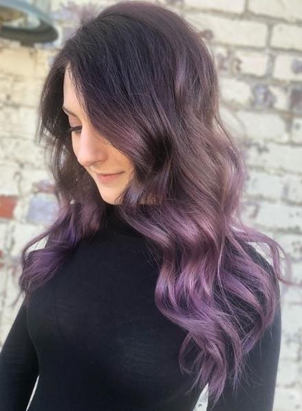 Femme avec de longs cheveux bouclés de balayage violet