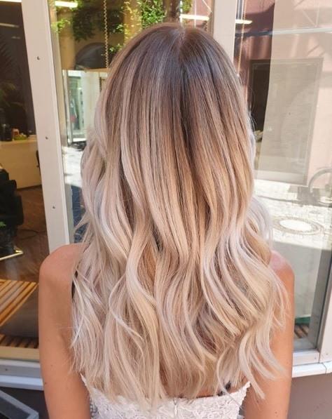 Femme aux longs cheveux ondulés et blonds clairs en balayage