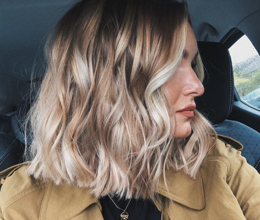 Woman with a wavy blonde balayage bob