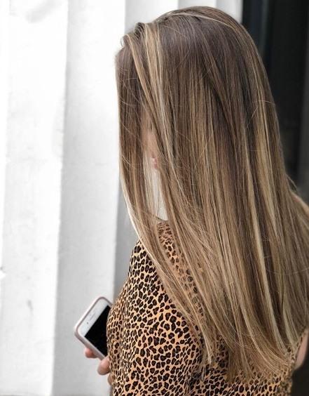 Femme aux longs cheveux bruns raides en balayage