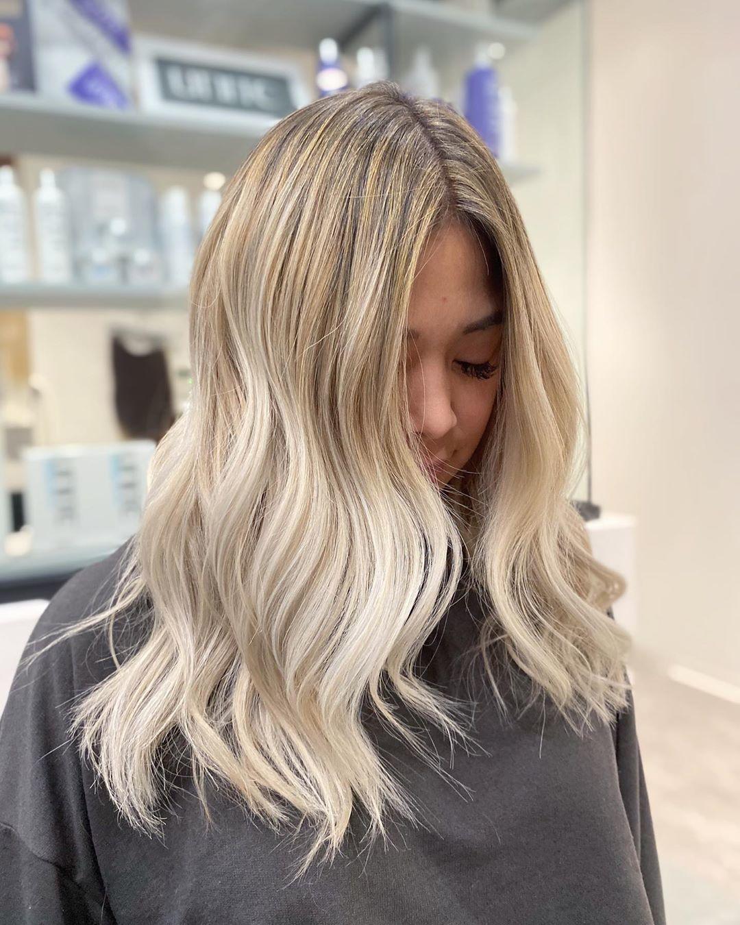 Femme aux cheveux blonds mi-longs ondulés de couleur beige
