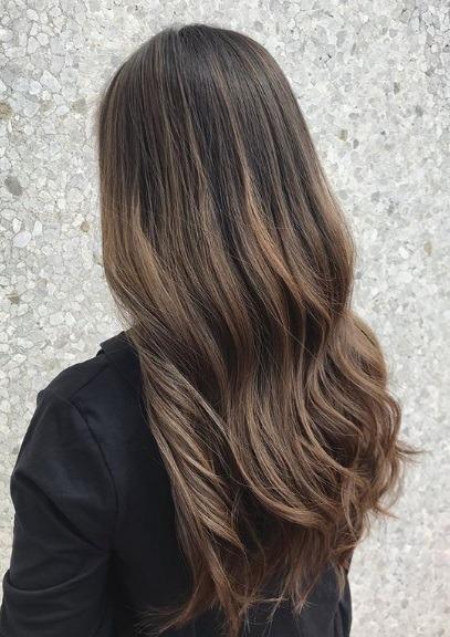 Femme aux longs cheveux bruns cendrés et ondulés en balayage
