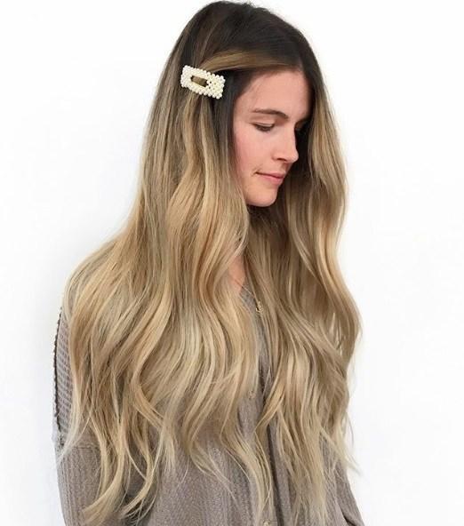 Femme avec de très longs cheveux blonds ondulés en balayage