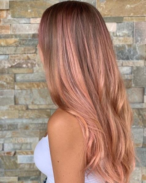 Femme aux longs cheveux en or rose de balayage