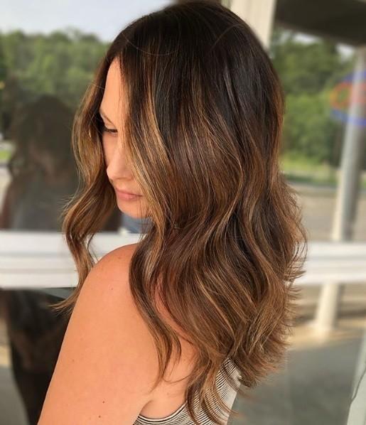 Femme aux cheveux mi-longs et ondulés de couleur caramel