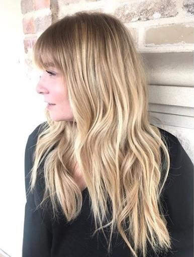 Femme aux longs cheveux blonds ondulés en balayage avec une frange