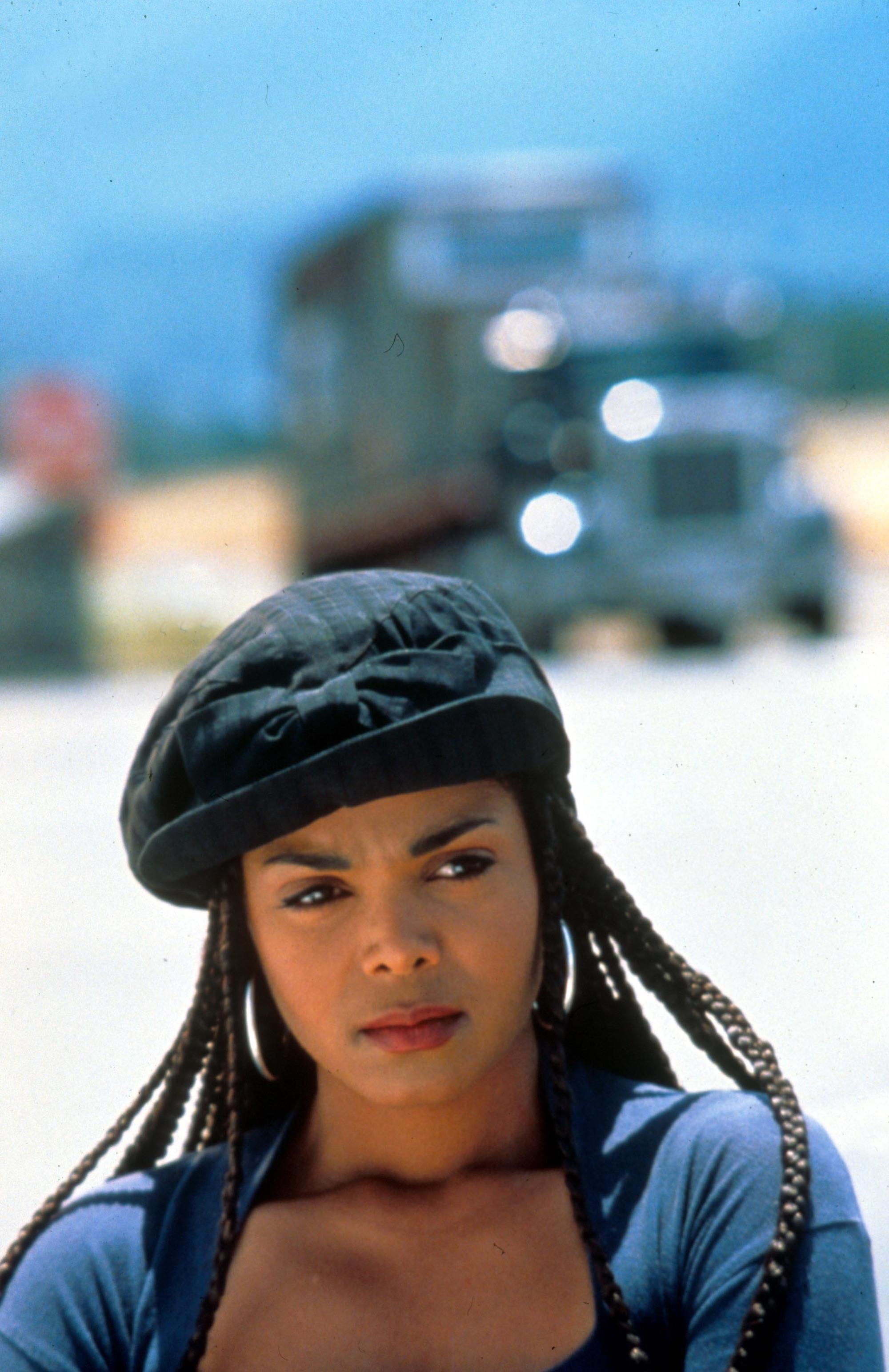 Coiffures des années 90 : Janet Jackson boxe des tresses du film Poetic Justice, portant un béret noir et des boucles d'oreilles en cerceau