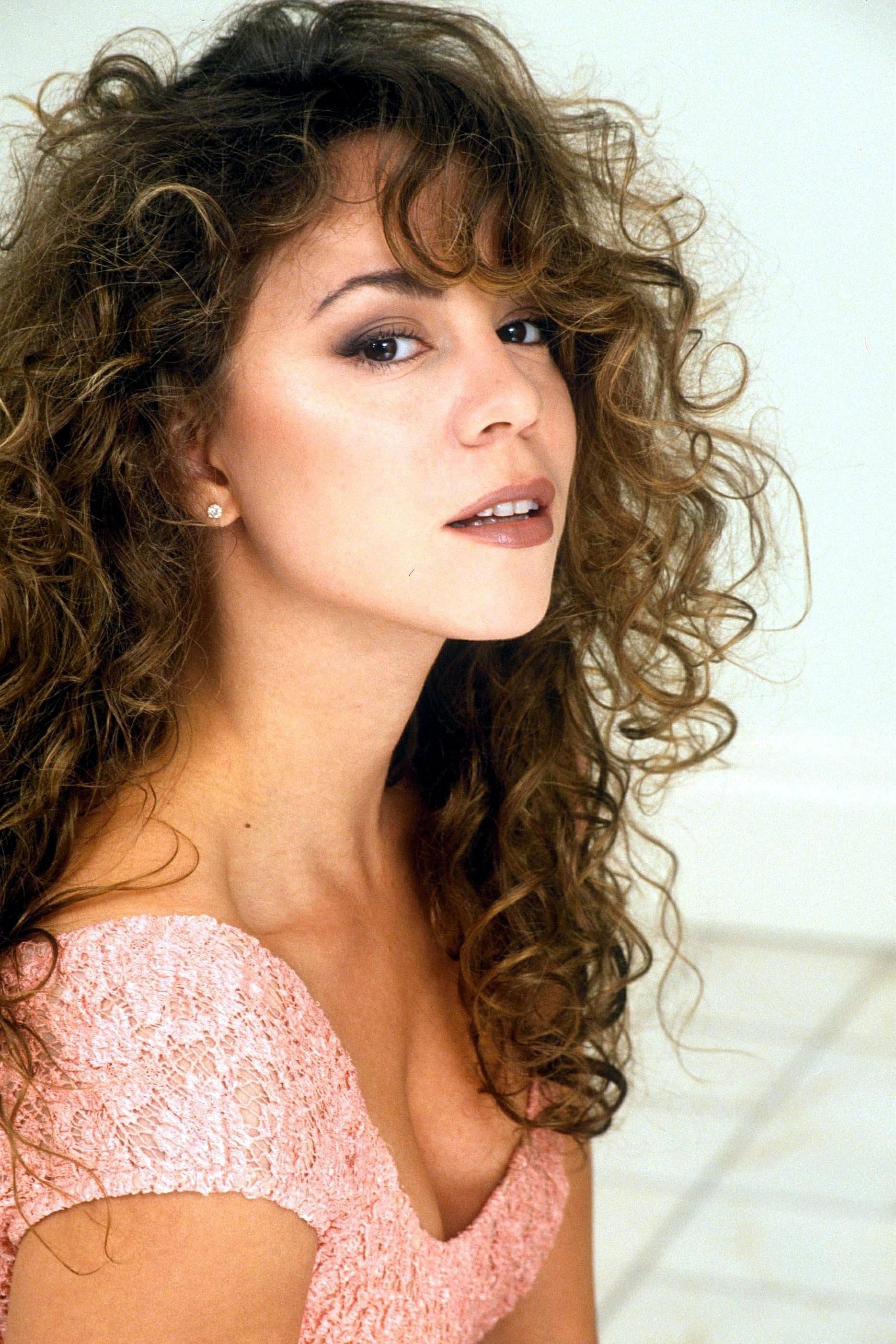Coiffures des années 90 : Mariah Carey, cheveux bruns naturellement bouclés avec une frange sur le côté, portant une robe rose