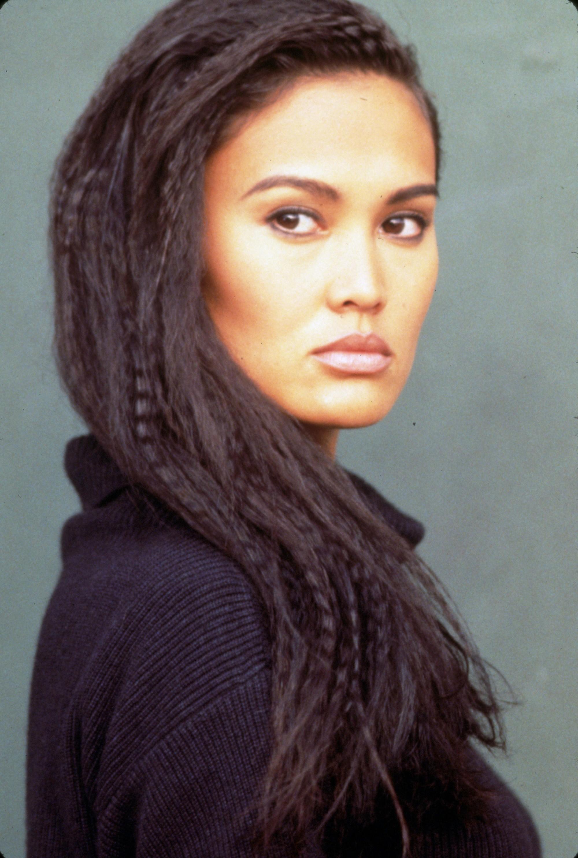 Tia Carrere avec de longs cheveux frisés dans les années 90