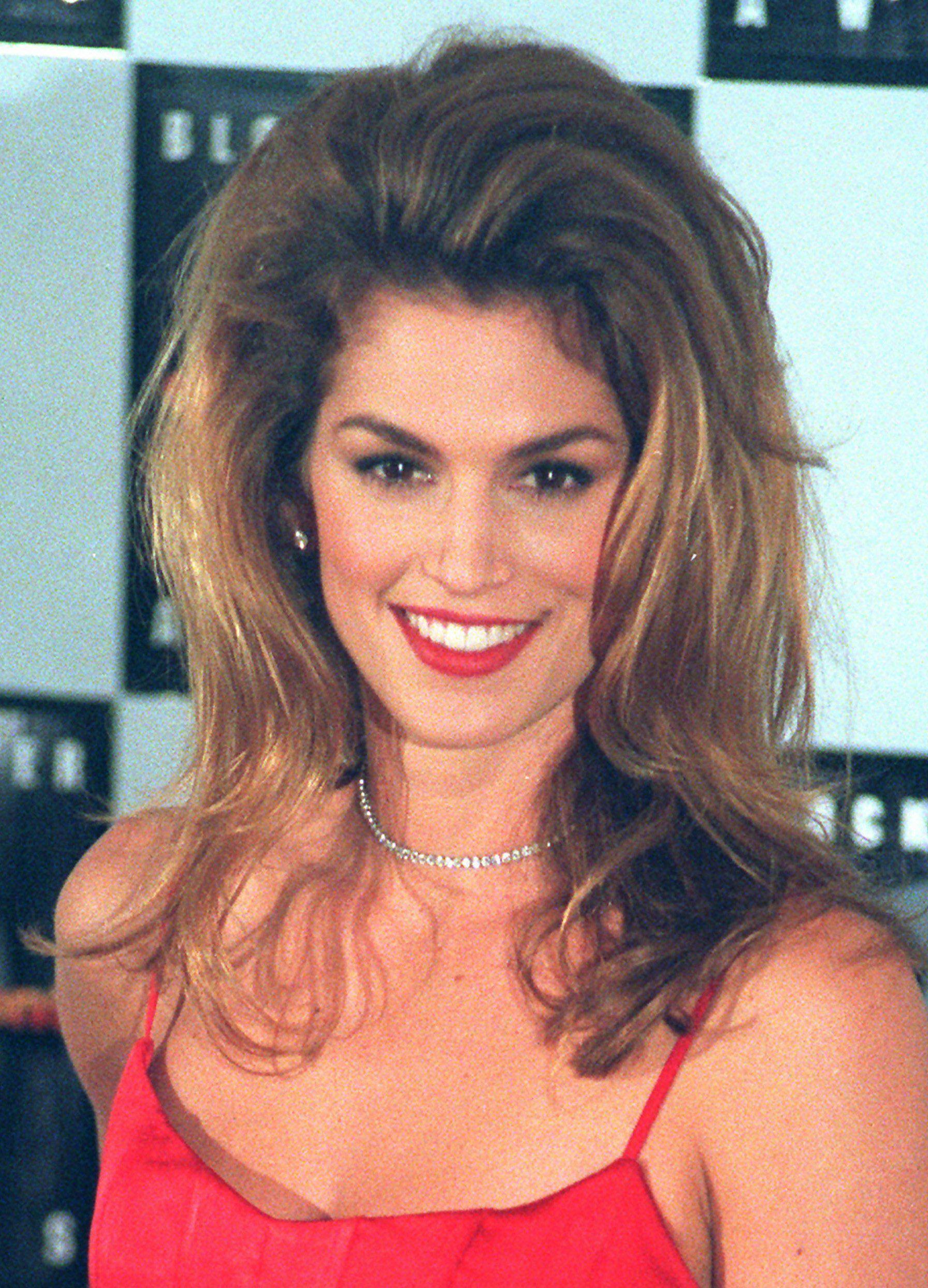 Coiffures des années 90 : Cindy Crawfod, une grande coiffure des années 90 sur des cheveux bruns. Cindy porte une robe camisole rouge et du rouge à lèvres rouge