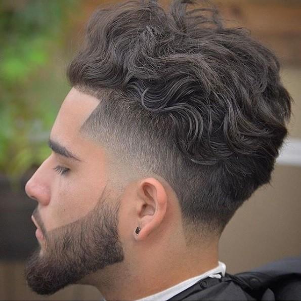 vue latérale d'un homme aux cheveux châtains moyens, dans un style mohawk bouclé avec une barbe fanée et façonnée