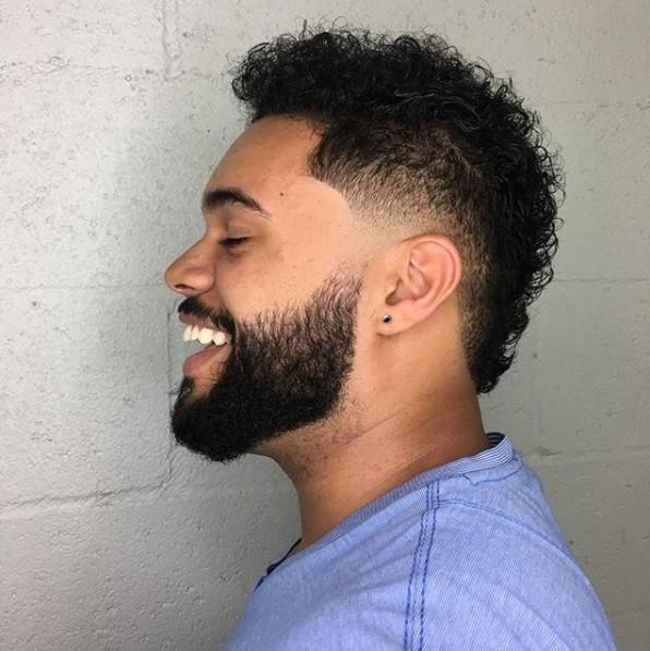 vue de côté d'un homme aux cheveux courts et bouclés coupés en fauxhawk avec une barbe