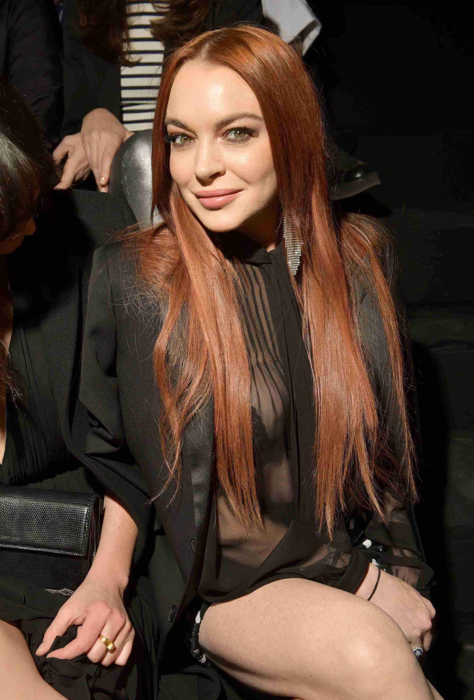 Les rousses célèbres : Lindsay Lohan avec de longs cheveux roux foncés raides, portant une tenue toute noire.