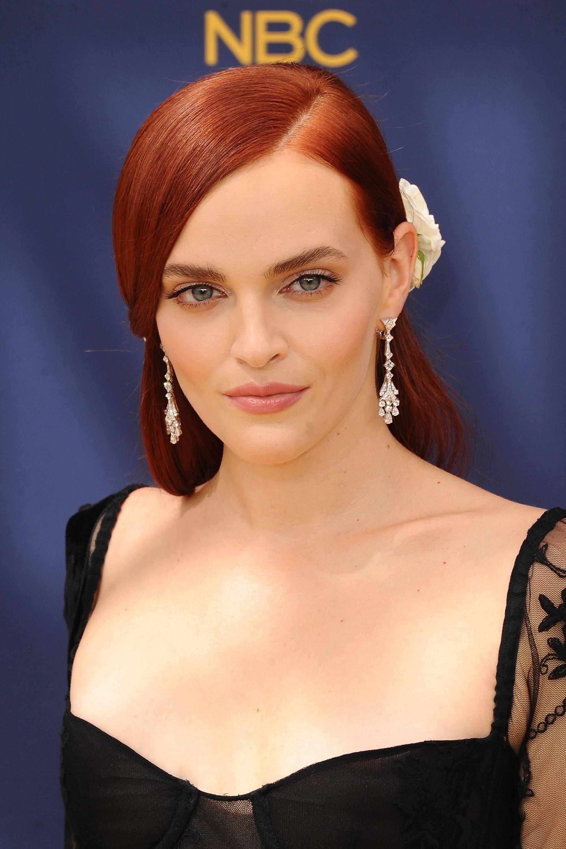 Les rousses célèbres : Madeline Brewer aux longs cheveux raides rouge foncé, coiffée en raie sur le côté avec un grand accessoire à fleurs blanches et portant une robe en dentelle noire.