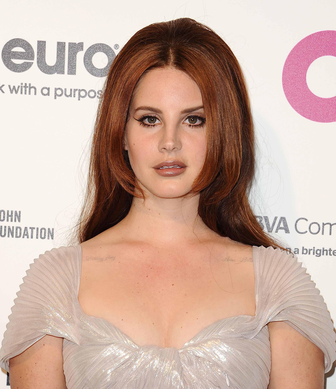 Les rousses célèbres : Lana Del Rey aux longs cheveux châtains raides avec une finition bouffante et volumineuse.