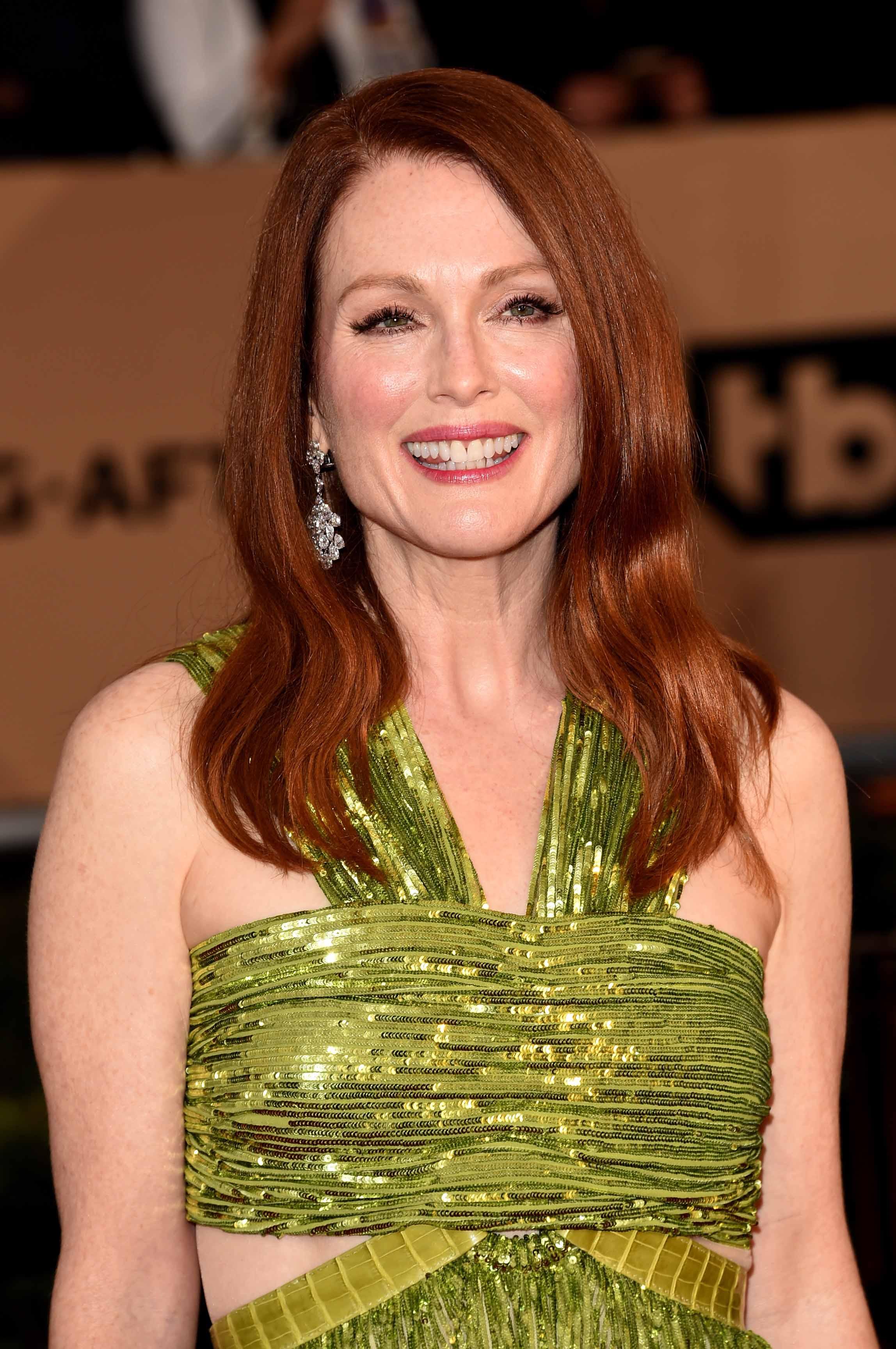 Les rousses célèbres : Julianne Moore avec des cheveux roux ondulés de longueur moyenne, portant une robe verte.