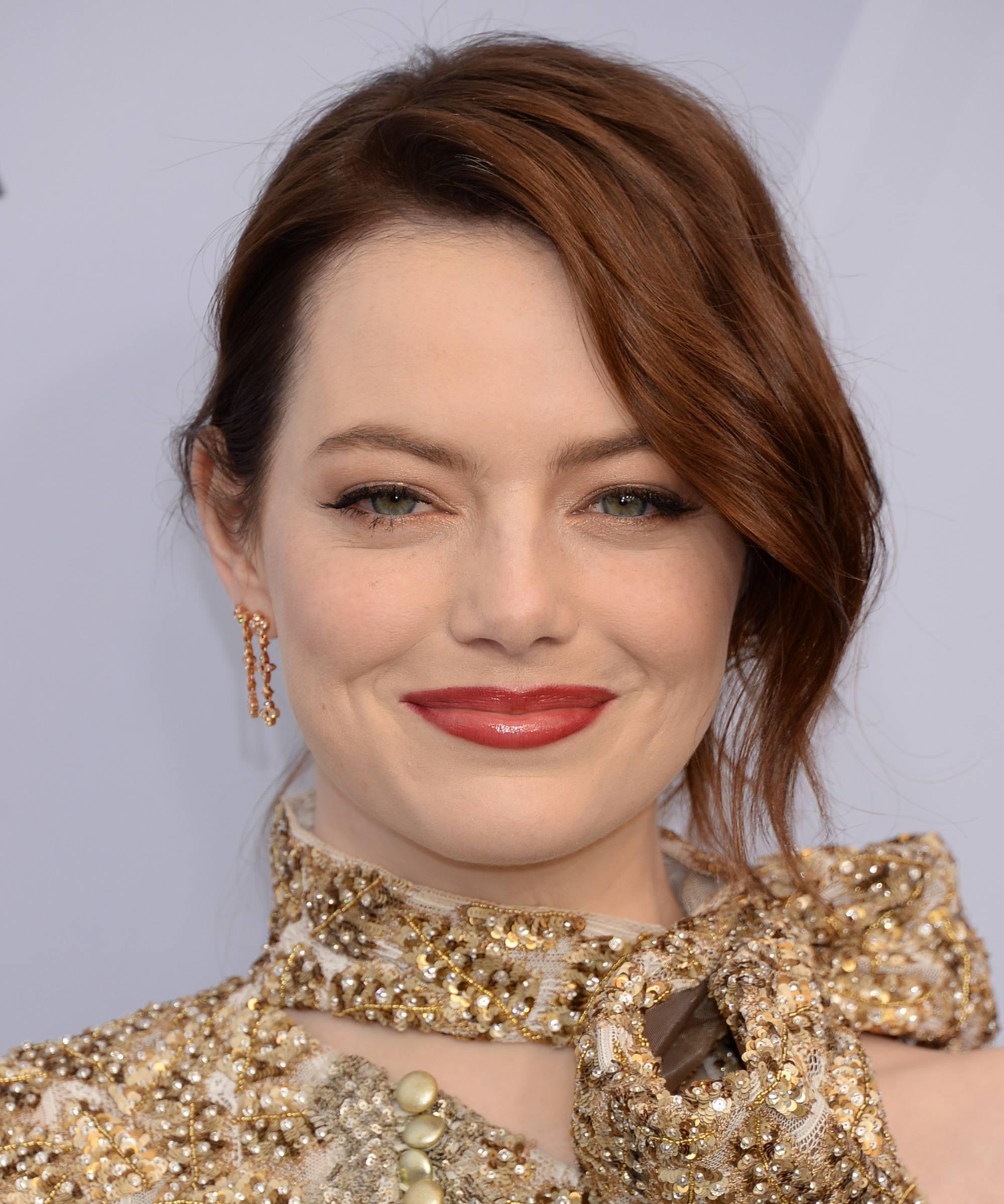 Les rousses célèbres : Emma Stone, aux cheveux ondulés rouge foncé, coiffée d'un updo avec une frange lâche sur le long côté et portant une robe dorée à col haut.