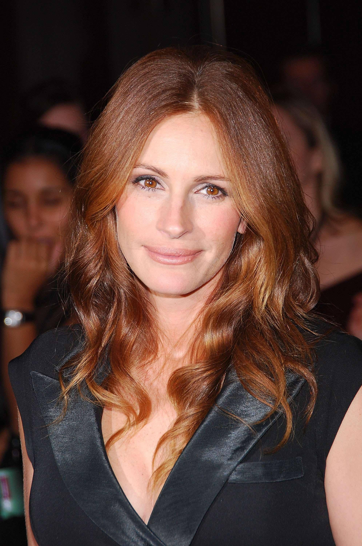 Les rousses célèbres : Julia Roberts avec des cheveux longs ondulés brun rouge auburn portant une robe noire brillante.