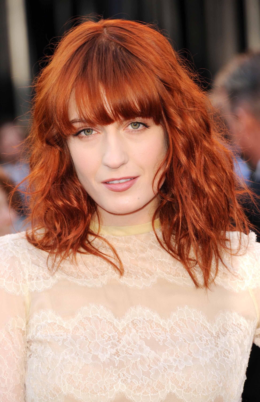 Les rousses célèbres : Florence Welch avec des cheveux mi-longs ondulés d'un rouge vif cuivré, avec une frange droite.