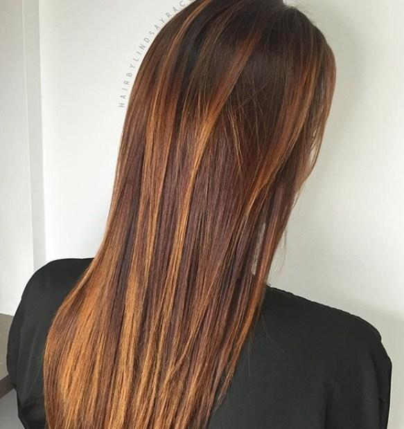 Cheveux bruns roux : Plan arrière d'une femme aux longs cheveux châtains avec des reflets rouges dorés.