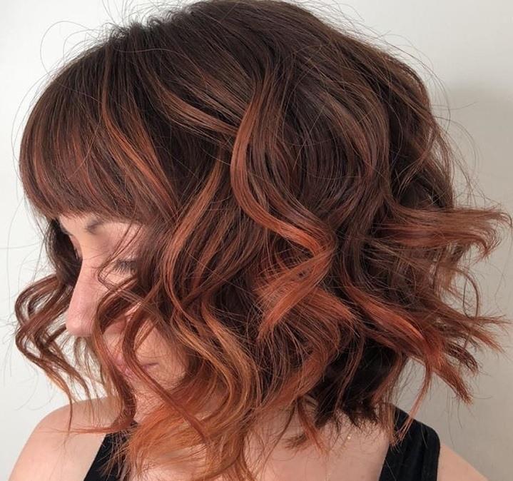 Cheveux bruns roux : Photo de côté d'une femme avec un petit bob bouclé brun foncé avec un balayage de cuivre.