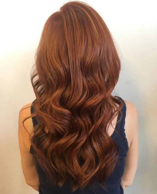 Cheveux bruns roux : Gros plan d'une femme aux longs cheveux auburn ondulés.
