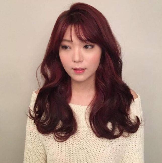 Cheveux bruns roux : Gros plan d'une femme aux cheveux roux acajou soufflés avec une frange sur le côté.