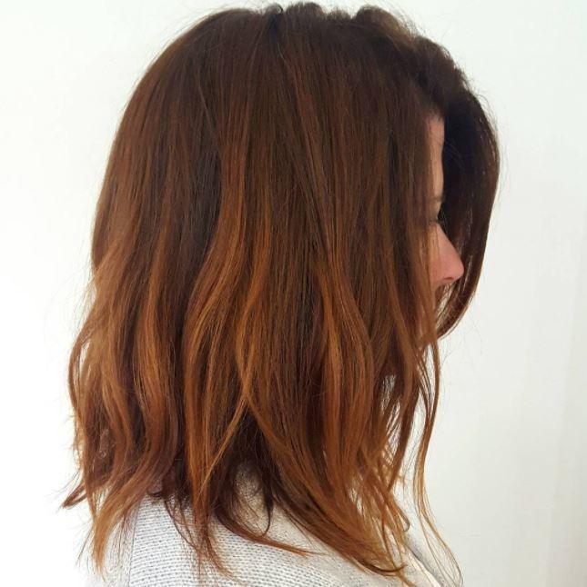 Cheveux bruns roux : Gros plan d'une femme avec des cheveux ébouriffés de la longueur d'un lobe de cannelle.