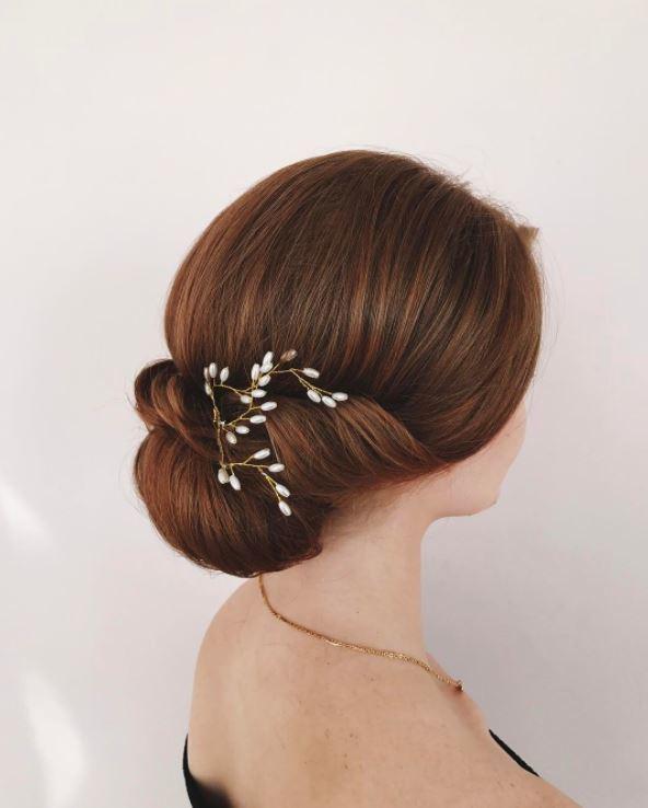 Cheveux bruns roux : Gros plan d'une femme aux cheveux châtains avec des reflets auburn, coiffée en chignon floral