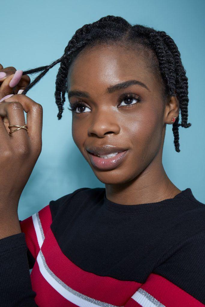femme aux cheveux noirs naturels coiffant ses cheveux en tordant de petites sections