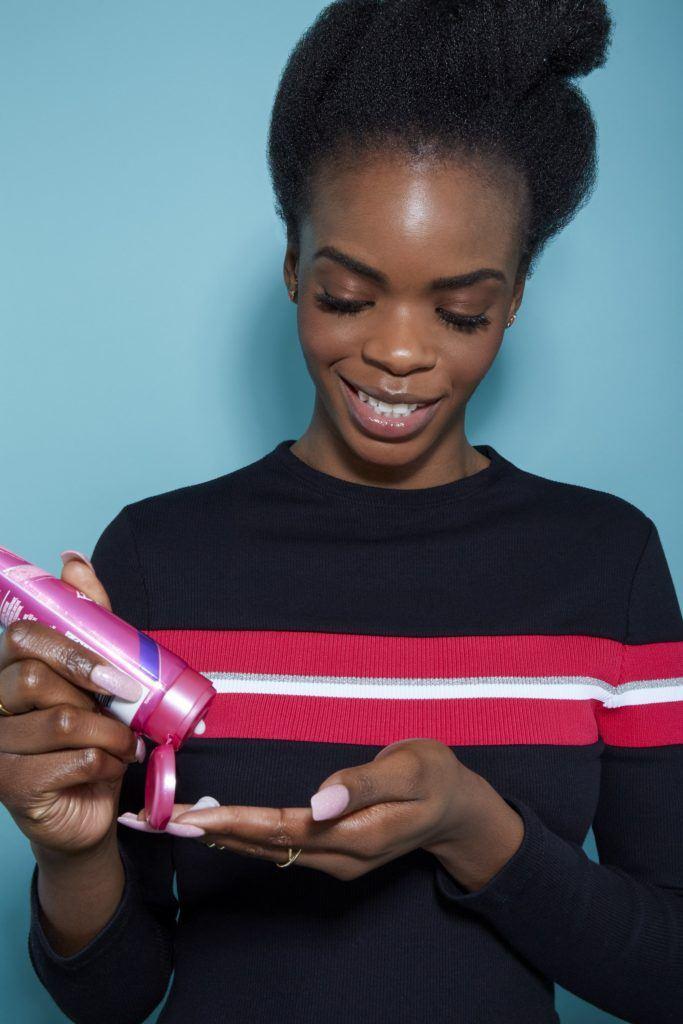 femme aux cheveux noirs naturels regardant vers le bas en appliquant un produit capillaire dans ses mains