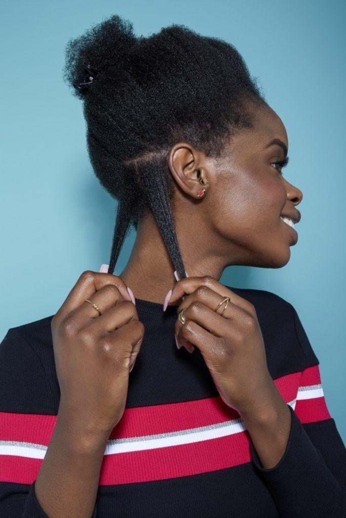 femme aux cheveux noirs naturels tirant deux sections de ses cheveux pour les coiffer