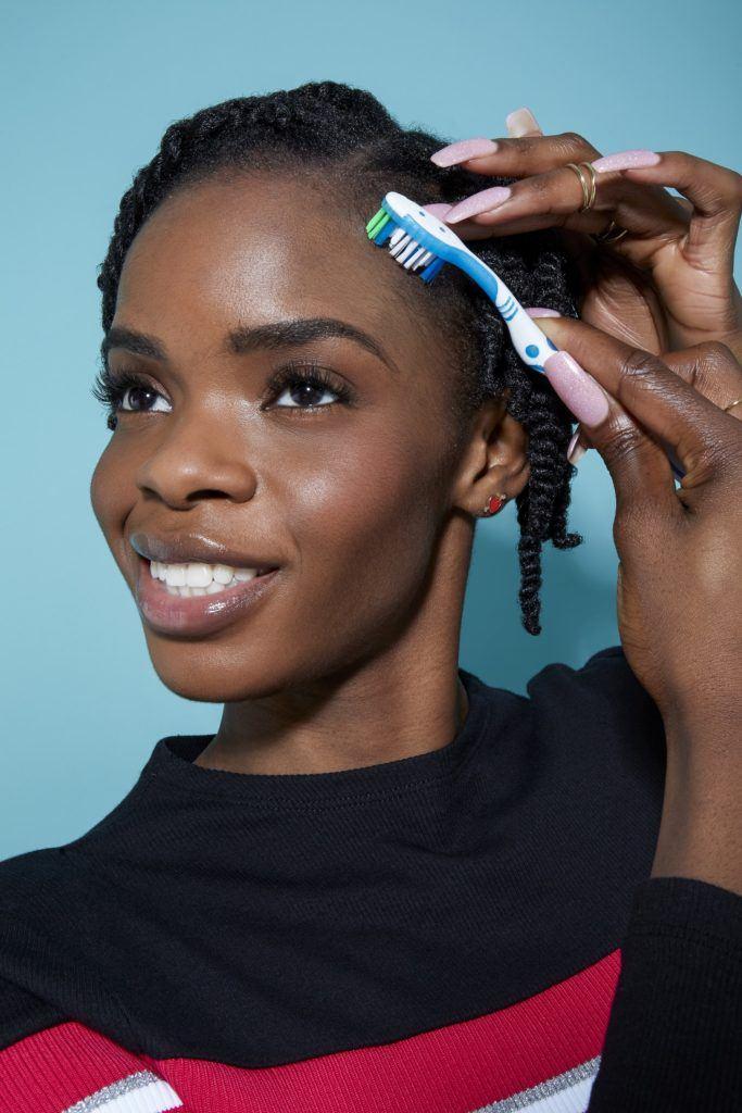 femme aux cheveux noirs naturels coiffée en petites mèches à l'aide d'une brosse à dents pour mettre en place les cheveux de son bébé