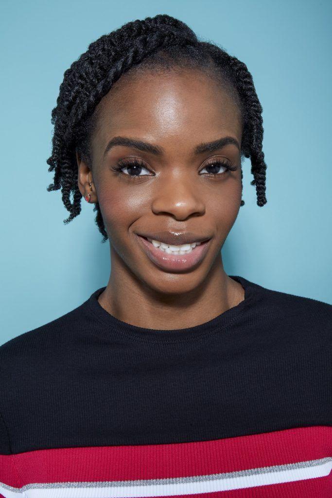 femme aux cheveux noirs naturels coiffée en petites mèches, regardant la caméra en souriant