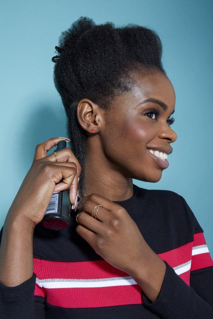 Une femme aux cheveux noirs naturels vaporisant un après-shampoing à ses cheveux