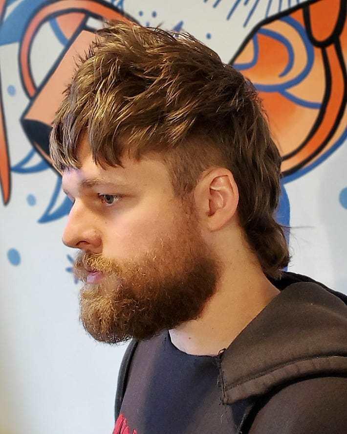 Homme aux cheveux bruns avec un mulet et une barbe